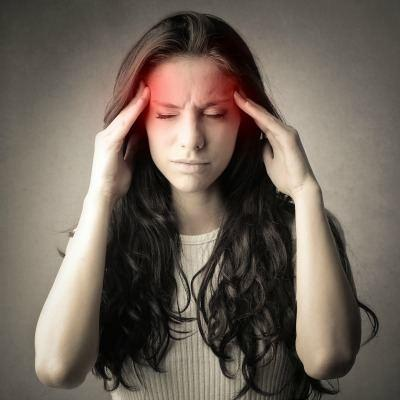 A woman with a headache in need of a chiropractic adjustment