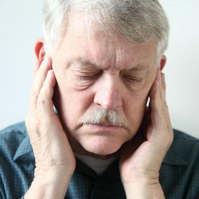 Older man with TMJ issuse thinking about going to his chiropractor.