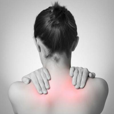 Young woman rubbing her upper back due to pain from a pinched nerve.